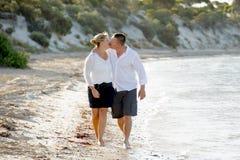 在走在海滩的爱的有吸引力的美好的夫妇亲吻在浪漫暑假 免版税库存图片