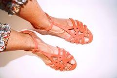 在走在白色背景的桃红色凉鞋的腿 免版税库存图片