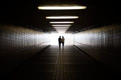 在走往步行地下过道出口的剪影的年轻夫妇  免版税图库摄影