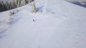 在走沿用雪盖的山的上面的孤独的旅游女孩的飞行 清楚的冷淡的天气 股票视频