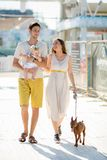 在走的爱的年轻时髦的行家夫妇演奏在热带海滩,白色沙子,凉快的成套装备,浪漫心情的狗小狗 免版税库存图片