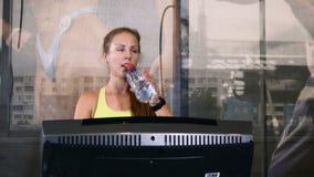 在走的轨道drinkink水的逗人喜爱的白肤金发的女运动员训练 生活方式概念 有吸引力的20s 4K 影视素材