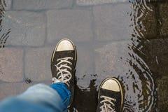 在走通过雨的运动鞋的男性腿搅浊 图库摄影