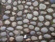 在走道的老破旧的圆的鹅卵石 库存照片