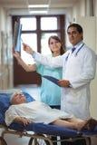 在走廊的医生和护士审查的报告 免版税图库摄影