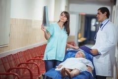 在走廊的医生和护士审查的报告 免版税库存照片