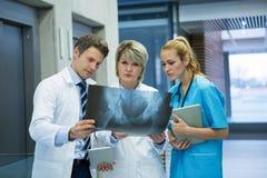 在走廊的医疗队审查的X-射线报告 库存图片