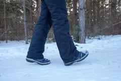 在起动的妇女腿关闭积雪的道路在冬天森林,背面图里 免版税图库摄影