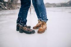 在起动的男性和女性腿和牛仔裤在冰背景中 库存照片