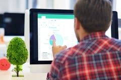 在起始的办公室分析在计算机上的一个商人的背面图图表 免版税图库摄影