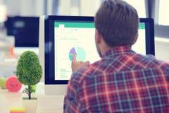 在起始的办公室分析在计算机上的一个商人的背面图图表 图库摄影