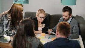 在起始的办公室群策群力谈论的小组年轻建筑师创造性的小企业队会议新的想法 股票录像