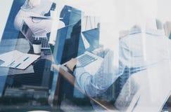 年轻在起始的项目的工友运转的膝上型计算机在现代地方 配合企业概念 摩天大楼办公楼在 免版税库存图片