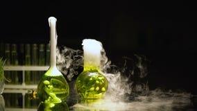 在起泡和在黑暗,反应中的烧瓶的化工液体散发烟 股票录像