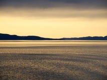 在起波纹的水的橙色日落焕发 免版税库存照片