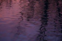 在起波纹的水的紫色反射 图库摄影