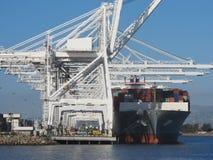 在起重机旁边被装载和靠码头的货船在口岸 免版税图库摄影
