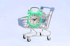 在超级市场台车的绿色闹钟在蓝色背景 库存图片