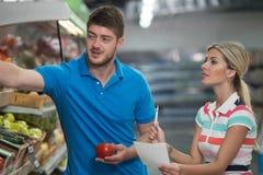 在超级市场的夫妇购物有杂货名单的 库存图片