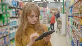 在超级市场的妇女购物和使用在她的片剂、技术和零售概念的流动apps 影视素材