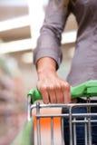 在超级市场的妇女购物有台车的 库存照片