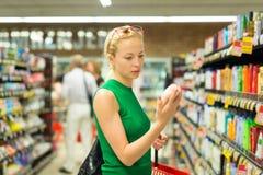 在超级市场的妇女购物的个人卫生产品 免版税库存照片