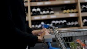 在超级市场的少妇购物 认为什么她应该其次买,走与台车在酒铺附近 影视素材