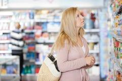 在超级市场的少妇购物 图库摄影