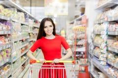 在超级市场的愉快的妇女购物 免版税库存照片