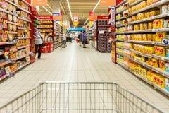 在超级市场走道的购物车视图 库存图片