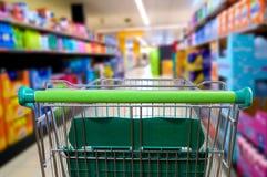 在超级市场走道背面图的购物车 免版税库存图片