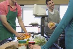 在超级市场结算离开的家庭 免版税库存照片