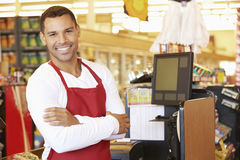 在超级市场结算离开的男性出纳员 库存照片