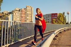 在超级英雄服装的女孩赛跑者沿路运行 免版税图库摄影