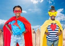 在超级英雄服装的孩子用在他们的站立反对天空的腰部的手在背景中 库存照片