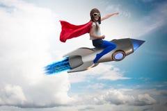 在超级英雄概念的小女孩飞行火箭 库存照片