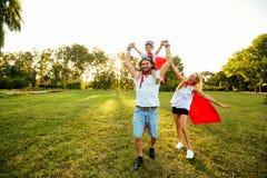 在超级英雄衣服的愉快的家庭在日落的公园 库存图片