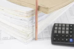 在超载老文书工作的信封与垂直的铅笔和计算器 库存图片