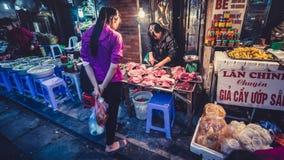 在越南市场上的生肉 妇女顾客购买2017年1月06日的生肉 免版税库存图片