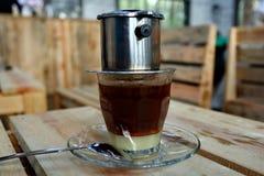 在越南样式的咖啡水滴在木桌上 免版税库存照片