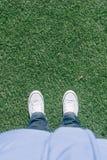 在足球场的人为草皮草与两双鞋子 库存图片