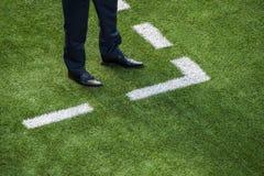 在足球场的粉笔线旁边教练身分 免版税库存照片