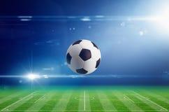 在足球场的足球有明亮的轻的火光的在夜 免版税库存图片
