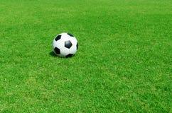 在足球场的足球 免版税库存图片
