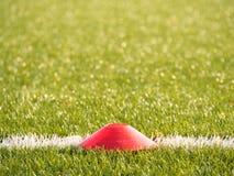 在足球场被绘的空白线路的明亮的红色塑料锥体  塑料橄榄球绿色草皮操场 库存照片