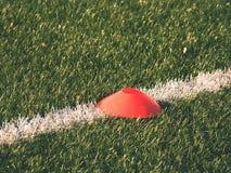 在足球场被绘的空白线路的明亮的红色塑料锥体  塑料橄榄球绿色草皮操场 免版税库存照片