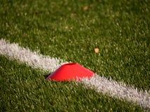 在足球场被绘的空白线路的明亮的红色塑料锥体  塑料橄榄球绿色草皮操场 免版税图库摄影