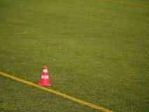 在足球场被绘的空白线路的明亮的红色塑料锥体  橄榄球绿色操场 免版税库存照片