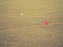 在足球场被绘的空白线路的明亮的红色塑料锥体  橄榄球绿色操场 库存图片