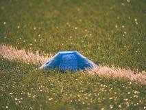 在足球场被绘的空白线路的明亮的蓝色塑料锥体  塑料橄榄球绿色草皮操场 免版税库存照片
